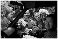 Peddlers offering sweet rice tubes for sale to traveler. Vietnam (black and white)