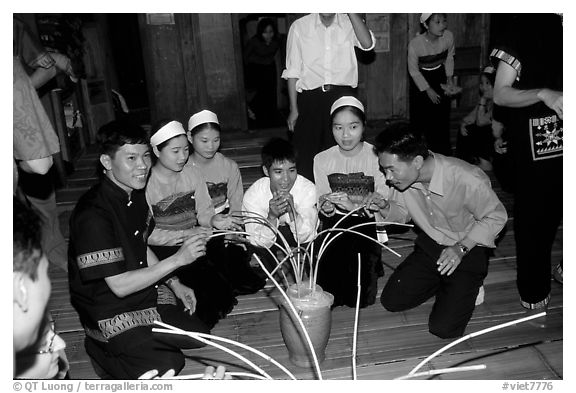 Thai women and guests drinking rau can alcohol with long straws, Ban Lac, Mai Chau. Northwest Vietnam (black and white)