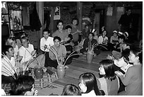 Guests in a thai house gather around jars of rau can alcohol, Ban Lac, Mai Chau. Northwest Vietnam (black and white)