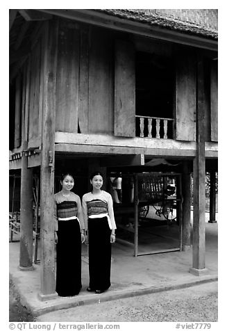 Two thai women standing in front of their stilt house, Ban Lac village. Northwest Vietnam (black and white)