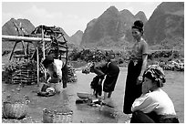 Thai women washing laundry and collecting water plants near an irrigation wheel, near Son La. Northwest Vietnam ( black and white)