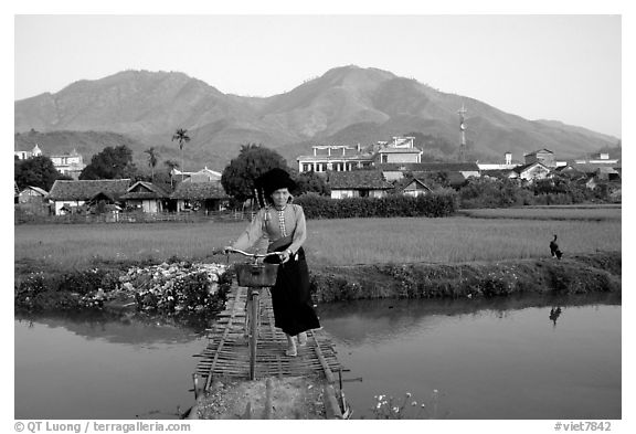 Thai woman pushing her bicycle across a bridge, Tuan Giao. Northwest Vietnam (black and white)