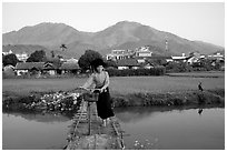 Thai woman pushing her bicycle across a bridge, Tuan Giao. Northwest Vietnam ( black and white)