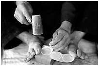 Hands and feet of a Black Dzao man making decorative coins, between Tam Duong and Sapa. Northwest Vietnam (black and white)