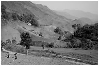 Two montagnards walking down a field, between Tuan Giao and Lai Chau. Northwest Vietnam (black and white)