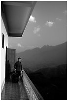 Traveler on a hotel balcony, looking at the Hoang Lien Mountains. Sapa, Vietnam ( black and white)