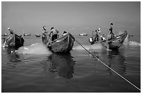 Fishermen get their nets out of their small fishing boats. Vung Tau, Vietnam (black and white)