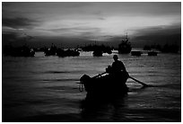 Man in a small boat, with moored boats seen against a vivid sunset. Vung Tau, Vietnam ( black and white)