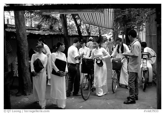 Uniformed school girls exit school. Ho Chi Minh City, Vietnam (black and white)