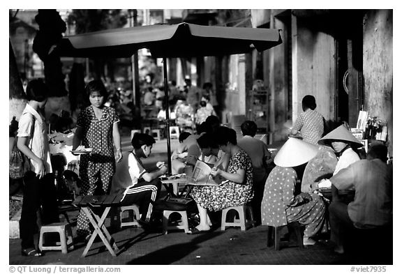 Eating in a street restaurant. Ho Chi Minh City, Vietnam (black and white)