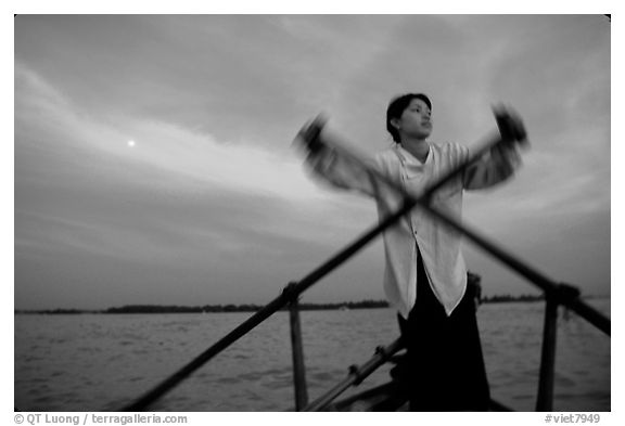 Boater using the X-shaped paddle characteristic of the Delta, sunset. Can Tho, Vietnam (black and white)