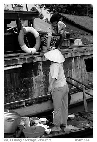 Passsing a bowl of pho from boat to boat. Can Tho, Vietnam (black and white)