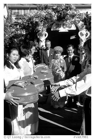 Gifts are exchanged as a newly wedded couple exits the bride's home. Ho Chi Minh City, Vietnam (black and white)