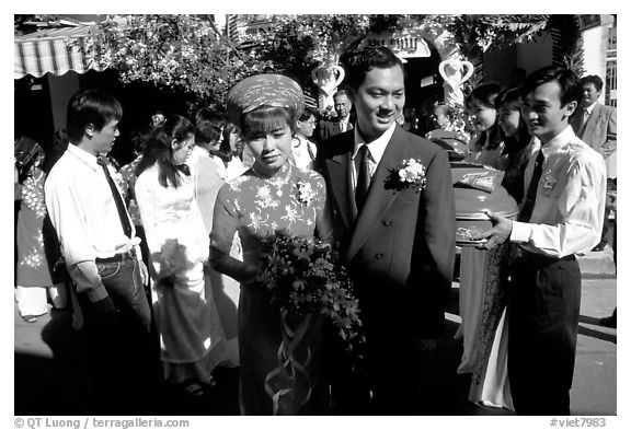 Newly-wed couple exit the bride's home. Ho Chi Minh City, Vietnam (black and white)