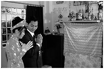 Newly-wed couple prays at the groom's ancestral altar. Ho Chi Minh City, Vietnam (black and white)