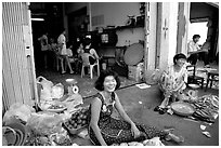 Old and new: street vendors and kids playing in a video games store. Ho Chi Minh City, Vietnam (black and white)
