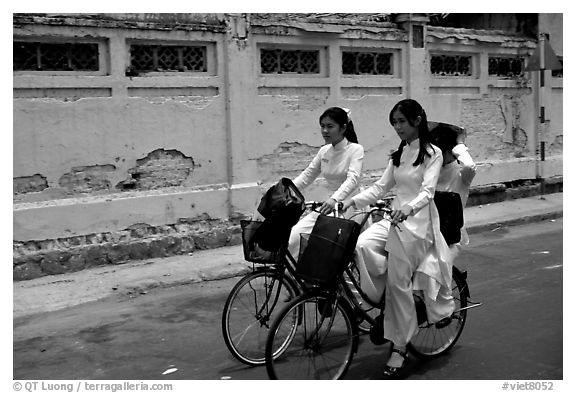 Senior high school girls ride bicycles with impeccable style, wearing elegant Ao Dai uniforms. Ho Chi Minh City, Vietnam (black and white)
