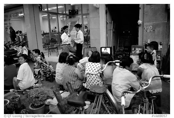 Watching TV on the street with the neighboors. Ho Chi Minh City, Vietnam (black and white)