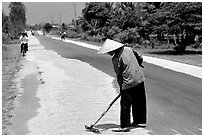 Rice being dried on sides of road. Mekong Delta, Vietnam ( black and white)