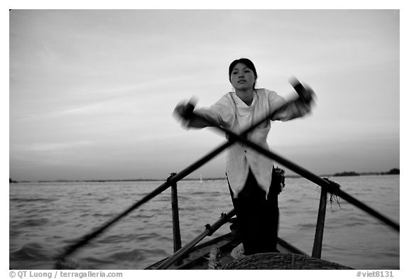 Woman using the X-shaped  paddle characteristic of the Delta. Can Tho, Vietnam (black and white)
