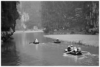 Villagers go to work floating a shallow river in Tam Coc. Ninh Binh,  Vietnam ( black and white)