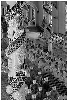 Priests and ornate columns inside the Great Caodai Temple. Tay Ninh, Vietnam ( black and white)