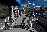 Woman and kids with mountain bikes on downtown Banff sidewalk. Banff National Park, Canadian Rockies, Alberta, Canada ( color)