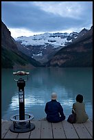 Couple sitting at the edge of Lake Louise at dawn. Banff National Park, Canadian Rockies, Alberta, Canada ( color)