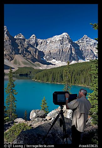 Photographer operating a 8x10 view camera at Moraine Lake. Banff National Park, Canadian Rockies, Alberta, Canada (color)