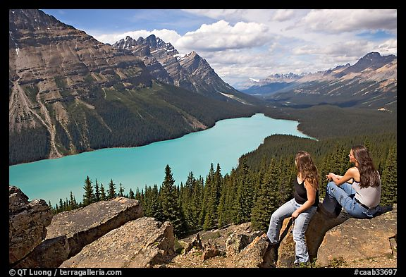 Tourists sitting on a rook overlooking Peyto Lake. Banff National Park, Canadian Rockies, Alberta, Canada (color)