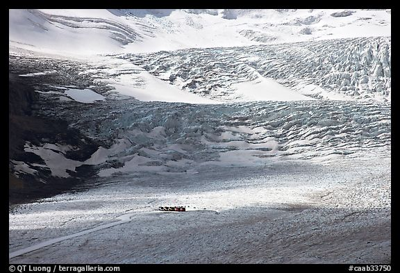 Distant view of snowcoaches parked at the base of the lower icefall on the Athabasca Glacier. Jasper National Park, Canadian Rockies, Alberta, Canada (color)