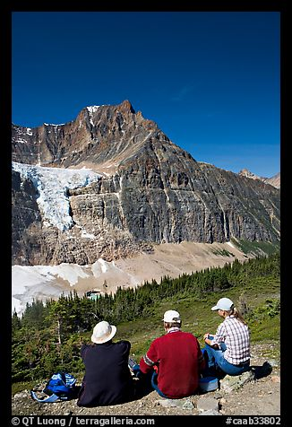 Hikers sitting in front of Mt Edith Cavell next to trail. Jasper National Park, Canadian Rockies, Alberta, Canada (color)