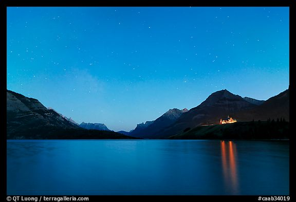 Waterton lake by night with stars in the sky in lights of Price of Wales Hotel. Waterton Lakes National Park, Alberta, Canada (color)