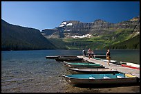 Dock and small boats, with tourists walking down, Cameron Lake. Waterton Lakes National Park, Alberta, Canada