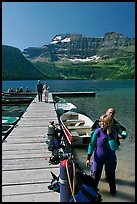 Couple preparing to scuba dive, Cameron Lake. Waterton Lakes National Park, Alberta, Canada