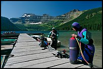 Scuba divers getting ready to dive, Cameron Lake. Waterton Lakes National Park, Alberta, Canada