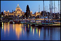 Boats in inner harbor with a trail of lights and parliament building lights. Victoria, British Columbia, Canada