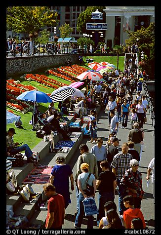 Tourists and art exhibitors on the quay of inner harbour. Victoria, British Columbia, Canada (color)