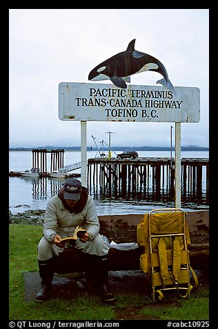 Backpacker sitting under the Transcanadian terminus sign, Tofino. Vancouver Island, British Columbia, Canada