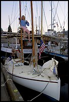 Girl swinging from the mast of a small sailboat, Inner Harbour. Victoria, British Columbia, Canada (color)