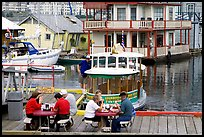 People eating fish and chips on deck,  Fisherman's wharf. Victoria, British Columbia, Canada ( color)