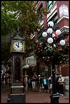 Tourists watch steam clock in Water Street. Vancouver, British Columbia, Canada