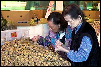 Two elderly women choosing tropical fruit. Vancouver, British Columbia, Canada ( color)