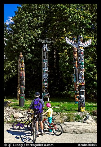 Family with bicycles looking at Totems, Stanley Park. Vancouver, British Columbia, Canada (color)