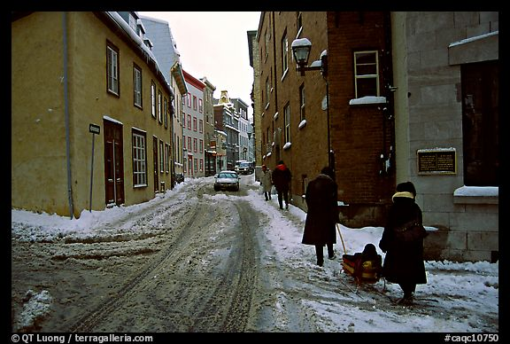 Residents pulling a sled with a child in a street, Quebec City. Quebec, Canada (color)