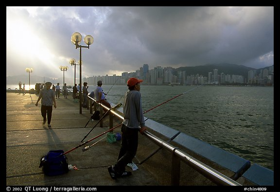 Fishing on the waterfront promenade, sunrise. Hong-Kong, China (color)