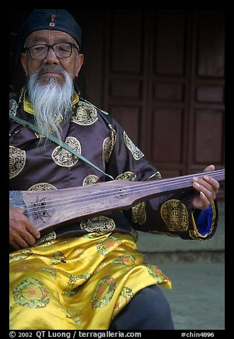 Elderly musician playing the a traditional guitar. Baisha, Yunnan, China