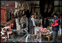 Loading roasted meat on a bicycle. Kunming, Yunnan, China