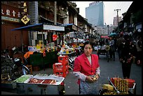 Street market in an old alley of wooden buildings, with a high rise in the background. Kunming, Yunnan, China ( color)
