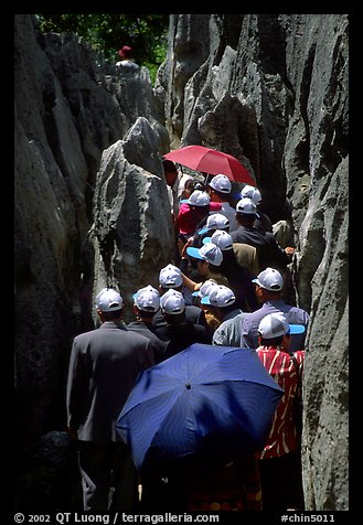 Crowds of Chinese tourists in a walkway among the limestone pillars. Shilin, Yunnan, China